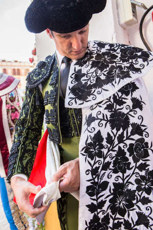 ancient tradition: Linares, provincia de Jaen, ESPA�A - 28 de agosto 2014: Toreador ponerse las cape pie en el callej�n antes de salir a luchar, tradici�n t�pica y muy antigua en Linares, provincia de Jaen, Espa�a