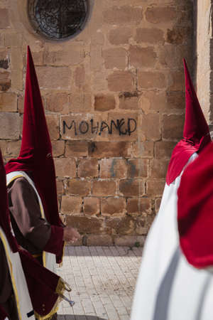 collectivity: Detail penitent red holding a candle during Holy Week, graffiti on the wall name Mohamed, take in Linares, Ja�n province, Spain Editorial