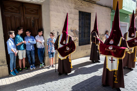 Set of boys watching Holy week procession, Spain, take in Linares, Jaen province, Spain