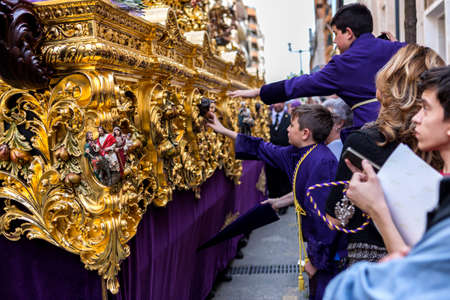 holy thursday: Linares, Jaen province, SPAIN - April 2, 2015: Boystries to touch the skirt of the throne to have good luck, popular tradition in Andalusia, Easter procession on Holy Thursday, taken in Linares, Jaen province, Andalucia, Spain