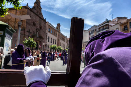 collectivity: Penitent praying on his cross in front of church during Holy week procession, Spain
