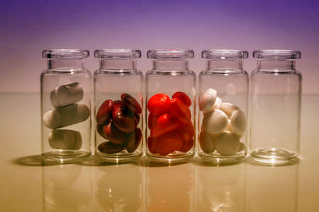 diferent: small bottles of diferent pills lined up Stock Photo