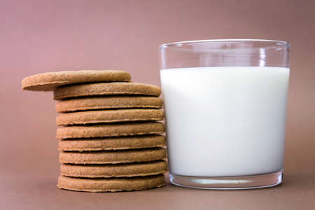 party food: Glass of milk and biscuits round Stock Photo