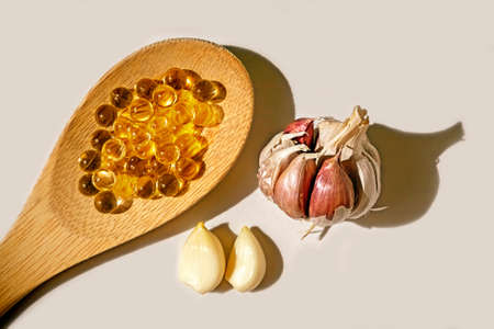 d: Pearls of garlic oil on wooden spoon, Garlic oil capsules, vitamins d pills