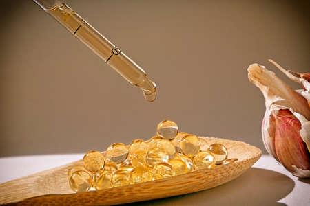vitamin d: Glass dropper on capsules of garlic oil, Garlic oil capsules, vitamins d pills