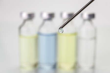 ampules: Needle of syringe with ampules on white blurred background Stock Photo