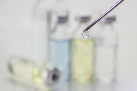 ampules: Needle of syringe with ampules on bicolor blurred background