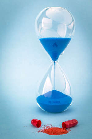 Hourglass marks the time of taking daily medication, isolated on blue background