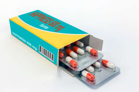 blister: Open medicine packet labelled happiness opened at one end to display a blister pack of tablets, isolated on white
