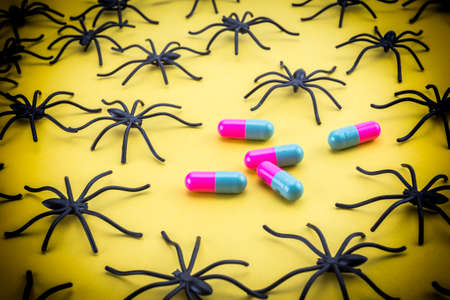 phobia: Spiders around capsules on yellow background, concept phobia to medicines Stock Photo