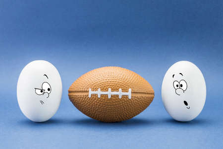 small group of objects: Two eggs look with strange face to a balloon of rugby Stock Photo