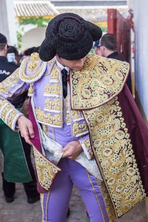 ancient tradition: Linares, SPAIN - August 28 2014: Spainish bullfighter Sebastian Castella putting itself the walk cape in the alley before going out to bullfight, typical and very ancient tradition in Linares,  Jaen province, Spain Editorial