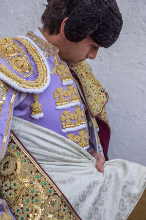bullfighter: Linares, SPAIN - August 28 2014: Spainish bullfighter Sebastian Castella putting itself the walk cape in the alley before going out to bullfight, typical and very ancient tradition in Linares,  Jaen province, Spain Editorial