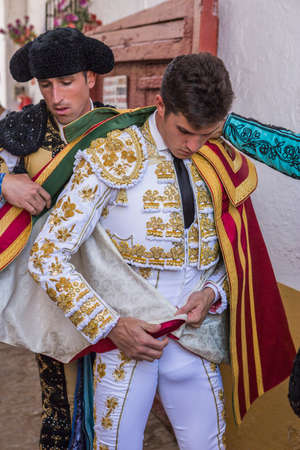 spainish: Linares, SPAIN - August 29 2014: Spainish bullfighter Daniel Luque putting itself the walk cape in the alley before going out to bullfight, typical and very ancient tradition in Linares,  Jaen province, Spain Editorial