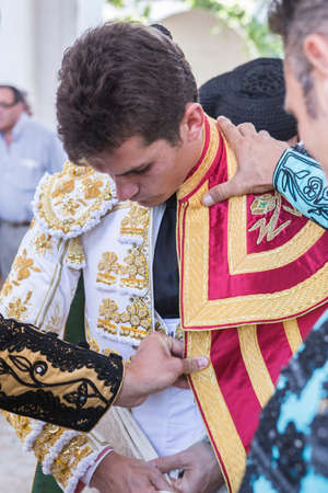 bullfighter: Linares, SPAIN - August 29 2014: Spainish bullfighter Daniel Luque putting itself the walk cape in the alley before going out to bullfight, typical and very ancient tradition in Linares,  Jaen province, Spain Editorial