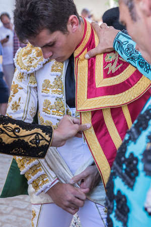 bullfight: Linares, SPAIN - August 29 2014: Spainish bullfighter Daniel Luque putting itself the walk cape in the alley before going out to bullfight, typical and very ancient tradition in Linares,  Jaen province, Spain Editorial
