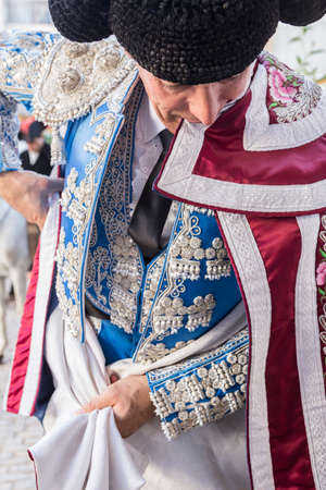 ancient tradition: Linares, SPAIN - August 29 2014: Spainish bullfighter putting itself the walk cape in the alley before going out to bullfight, typical and very ancient tradition in Linares,  Jaen province, Spain Editorial