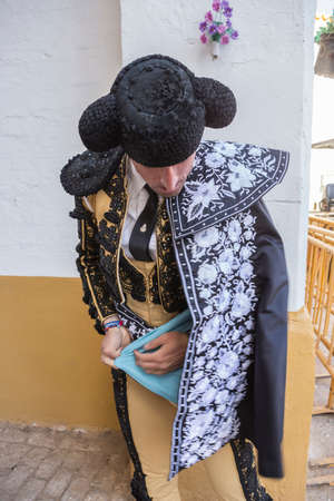 bullfighter: Linares, SPAIN - August 29 2014: Spainish bullfighter putting itself the walk cape in the alley before going out to bullfight, typical and very ancient tradition in Linares,  Jaen province, Spain Editorial