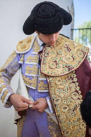 ancient tradition: Baeza, SPAIN - August 15 2014: Spainish bullfighter Sebastian Castella putting itself the walk cape in the alley before going out to bullfight, typical and very ancient tradition in Baeza,  Jaen province, Spain