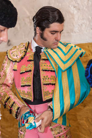 ancient tradition: Andujar, SPAIN - September 11, 2009: Spainish bullfighter Jose Antonio Morante de la Puebla putting itself the walk cape in the alley before going out to bullfight, typical and very ancient tradition in Andujar,  Jaen province, Spain