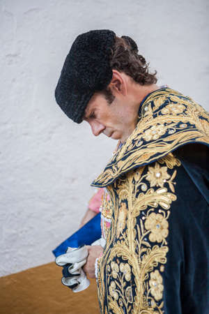 Linares, SPAIN - August 29 2014: Spainish bullfighter Jose Tomas putting itself the walk cape in the alley before going out to bullfight, typical and very ancient tradition in Linares,  Jaen province, Spain Imagens - 62234304