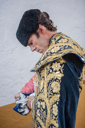 Linares, SPAIN - August 29 2014: Spainish bullfighter Jose Tomas putting itself the walk cape in the alley before going out to bullfight, typical and very ancient tradition in Linares,  Jaen province, Spain