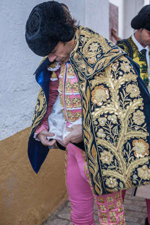 ancient tradition: Linares, SPAIN - August 29 2014: Spainish bullfighter Jose Tomas putting itself the walk cape in the alley before going out to bullfight, typical and very ancient tradition in Linares,  Jaen province, Spain
