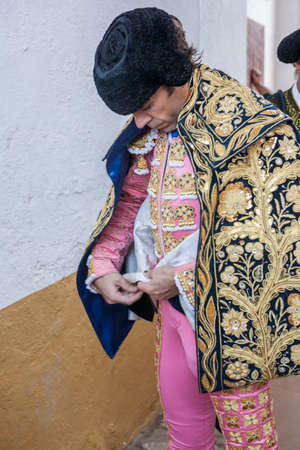 bullfighter: Linares, SPAIN - August 29 2014: Spainish bullfighter Jose Tomas putting itself the walk cape in the alley before going out to bullfight, typical and very ancient tradition in Linares,  Jaen province, Spain