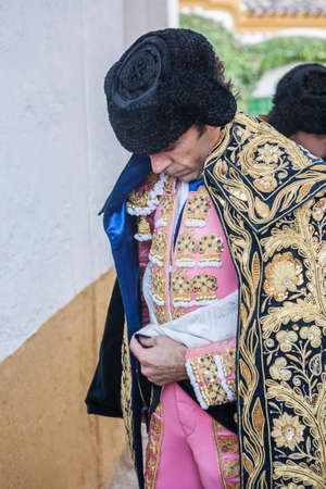 bullfight: Linares, SPAIN - August 29 2014: Spainish bullfighter Jose Tomas putting itself the walk cape in the alley before going out to bullfight, typical and very ancient tradition in Linares,  Jaen province, Spain