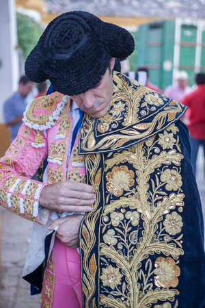 spainish: Linares, SPAIN - August 29 2014: Spainish bullfighter Jose Tomas putting itself the walk cape in the alley before going out to bullfight, typical and very ancient tradition in Linares,  Jaen province, Spain