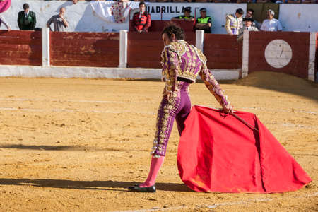 Andujar, Jaen province, SPAIN -  September 12, 2008: Spainish bullfighter Finito de Cordoba bullfighting with a crutch in a beautiful pass by low in the Bullring of Andujar, Jaen province, Andalusia, Spain Editorial