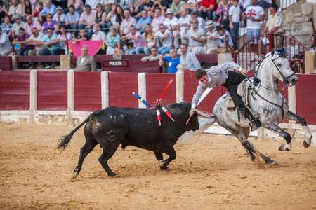 capote: Ubeda, Spain - October 2, 2010: Spanish bullfighter on horseback Leonardo Hernandez putting the bull banderillas in the bullring of Ubeda
