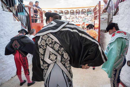 ancient tradition: Pozoblanco, SPAIN - September 29, 2010: Spainish bullfighter putting itself the walk cape in the alley before going out to bullfight, typical and very ancient tradition in Pozoblanco, Spain
