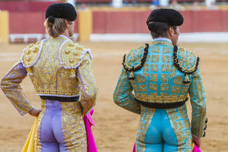 bullfighters: Andujar, SPAIN -  september 10, 2010: Spanish Bullfighters looking bullfighting, the Bullfighter on the left dressed in suit of lights of colors red and gold and the right color pistachio and gold in Andujar, Spain
