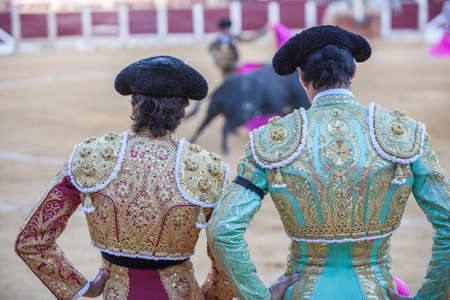 Ubeda, SPAIN - september 29, 2010: Spanish Bullfighters looking bullfighting, the Bullfighter on the left dressed in suit of lights of colors red and gold and the right color pistachio and gold in Ubeda, Spain Editorial