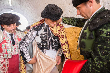 bullfighter: Andujar, SPAIN - September 7, 2014: Spainish bullfighter Miguel Abellan putting itself the walk cape in the alley before going out to bullfight, typical and very ancient tradition in Andujar, Spain Editorial