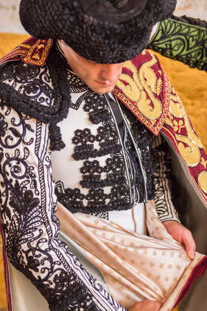 spainish: Andujar, SPAIN - September 7, 2014: Spainish bullfighter Miguel Abellan putting itself the walk cape in the alley before going out to bullfight, typical and very ancient tradition in Andujar, Spain Editorial