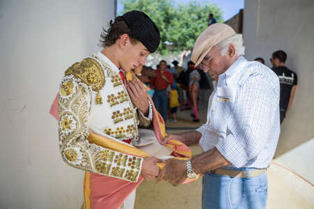 taught: Baeza, SPAIN - June 27, 2009: torero puts capote de paseo taught by his grandfather in the alley before going out to bullfight, typical and very ancient tradition in Baeza, Spain