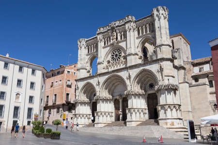 CUENCA, SPAIN - APRIL 2, 2016: Tourists walk near the facade of the Cuencas Cathedral, The cathedral is dedicated to St Julian, gothic english-norman style, XII century, called the Basilica of Our Lady of Grace Editorial