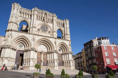 mancha: CUENCA, SPAIN - APRIL 2, 2016: Tourists walk near the facade of the Cuencas Cathedral, The cathedral is dedicated to St Julian, gothic english-norman style, XII century, called the Basilica of Our Lady of Grace Editorial