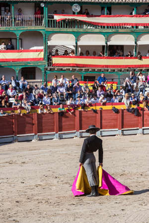 spainish: Chinchon, SPAIN - October 15, 2016: Spainish bullfighter Miguel Abellan with the cape in the main square of chinchon during the festival benefit traditional, Chinchon, Madrid province, Spain