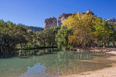fortitude: Alcala del Jucar, Spain - October 29, 2016: Recreation area on the River Jucar, beautiful mountain views limestone next to the city, at the top of mountain limestone is situated castle of Almohad origin of the century XII, take in Alcala of the Jucar, Alb