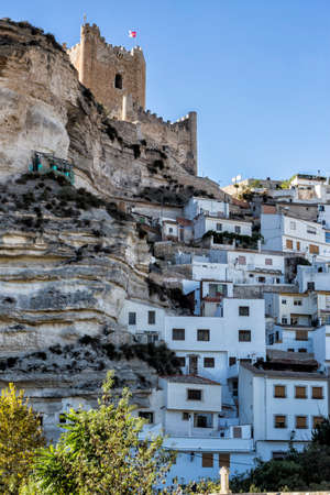 Alcala del Jucar, Spain - October 29, 2016: Side view of the village, on top of limestone mountain is situated Castle of the 12TH century Almohad origin, take in Alcala of the Jucar, Albacete province, Spain