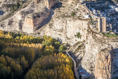 fortitude: Alcala del Jucar, Spain - October 29, 2016: Panoramic view of the valley of the river Jucar during autumn, on top of limestone mountain is situated Castle of the 12TH century Almohad origin, take in Alcala of the Jucar, Albacete province, Spain Editorial