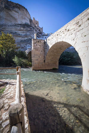 fortitude: Alcala del Jucar, Spain - October 29, 2016: Roman bridge, located in the central part of the town, to its passage by the river Jucar, at the top of mountain limestone is situated castle of Almohad origin of the century XII, take in Alcala of the Jucar, Al