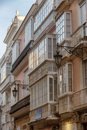 Cadiz Spain- March 31: Detail of balconies and large windows on the time of the nineteenth century, Narrow street with traditional architecture in Cadiz, Andalusia, southern Spain Editorial