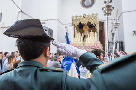 Linares, SPAIN - April 16: Soldiers of the Spanish civil guard salute when the national anthem at the exit of the Virgin of beautiful love, during Holy week in Linares, Andalusia, Spain