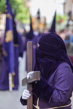 atonement: Penitent dressed in purple tunic of velvet resting on wooden cross during atonement station on Holy Week, Andalusia, Spain