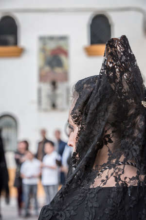Linares, SPAIN - April 12: Women dressed in typical suit of Spanish mantilla, to fund the bullring of Linares and poster of the anniversary of the death of Manolete during Holy Week, Linares, Andalucia, Spain Editorial