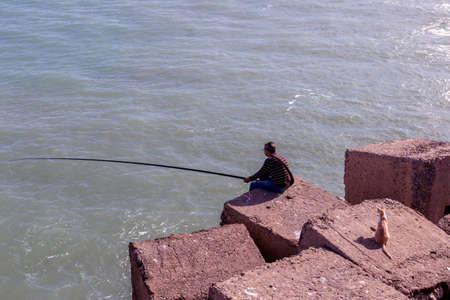 Man Fishing From Rocks On the edge of the sea bank, a cat watches attentively to steal fish, Take in cadiz, Andalusia, Spain